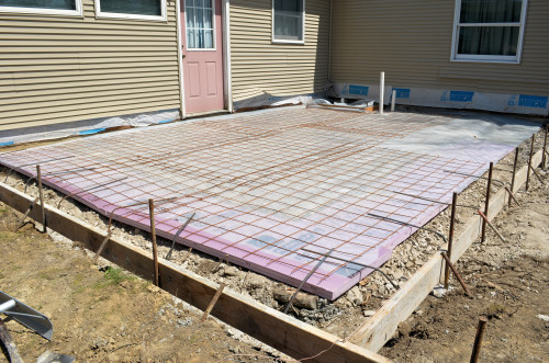Insulation and a wire reinforcing grid is laid on the crushed stone.