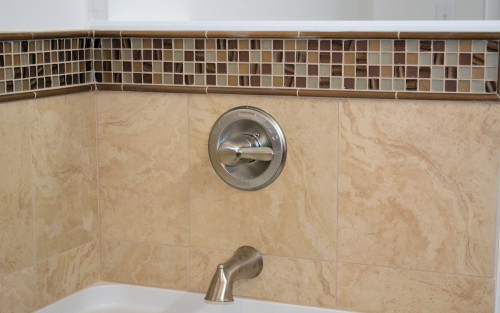 The mosaic trim around the tub matches the trim in the shower.