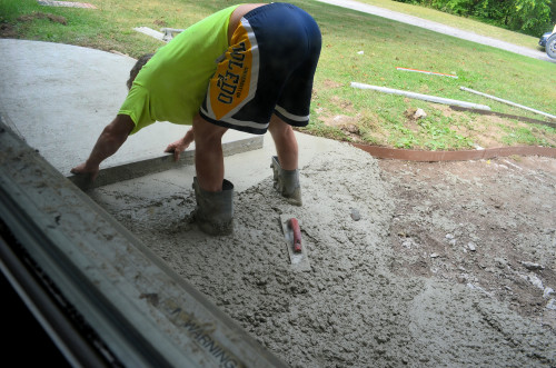 Using a screed to smooth the front walk.